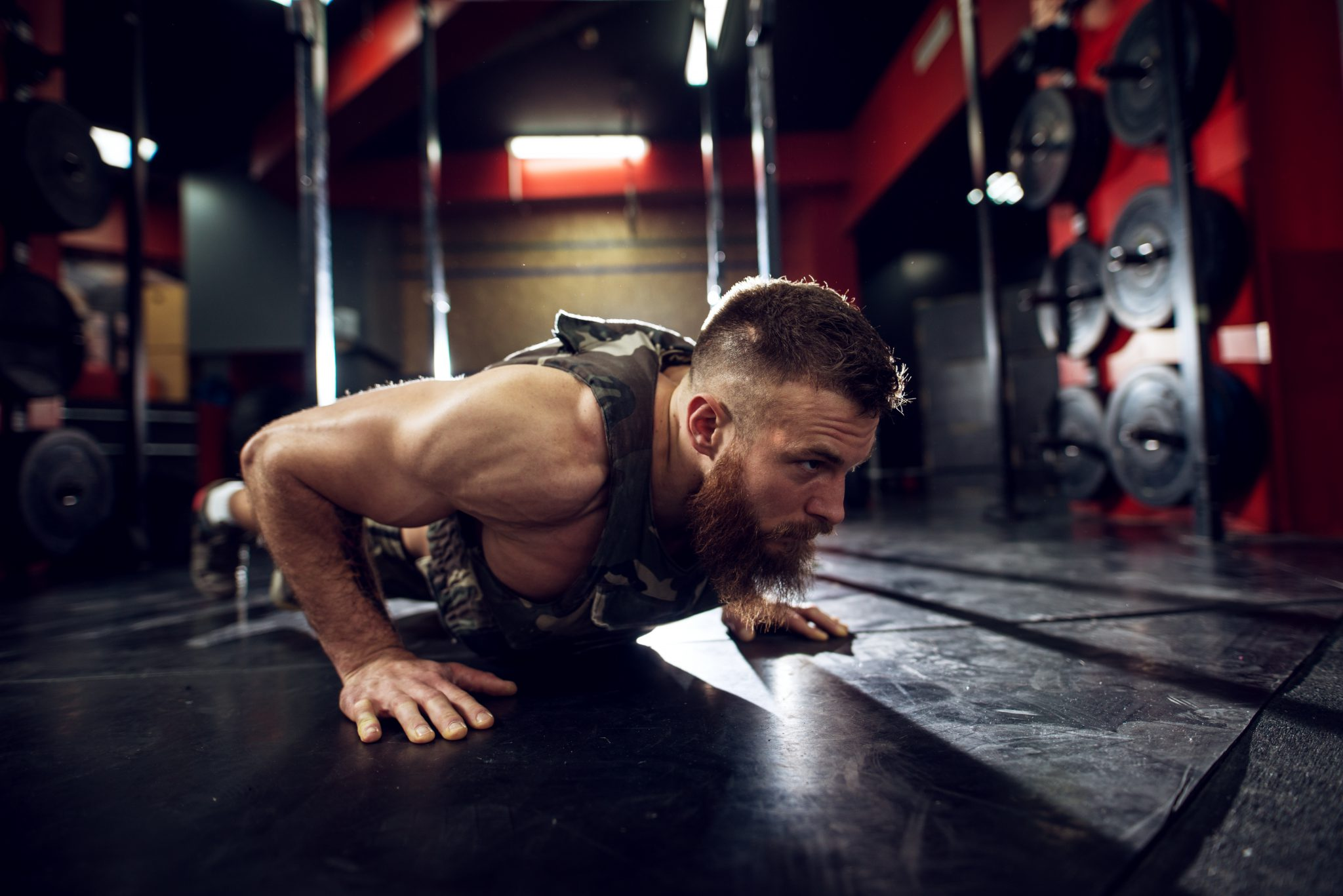 Portrait close up view of strong motivated muscular bearded short hair bodybuilder man doing push ups on the floor in the dark gym.